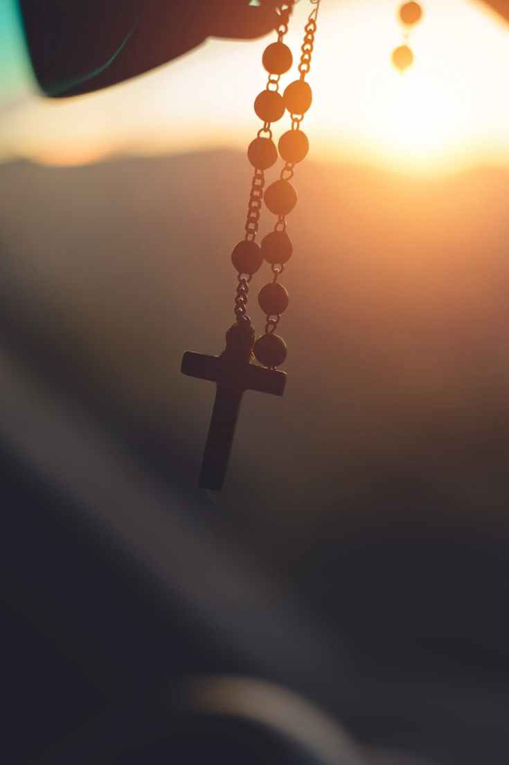 silhouette photography of hanging rosary